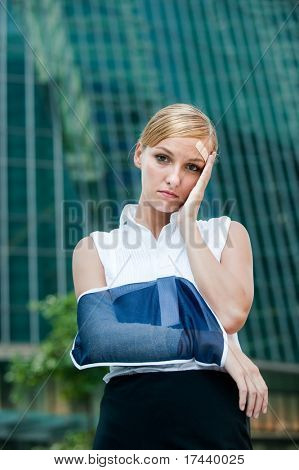 A young businesswoman with injured arm and band-aid standing in the city
