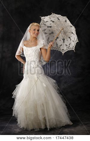 beautiful woman in wedding dress holding umbrella