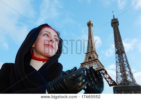 beautiful young woman holding souvenir, view of Eiffel Tower at winter