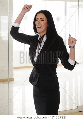 Young brunette businesswoman celebrate and dancing in office, cheerful person