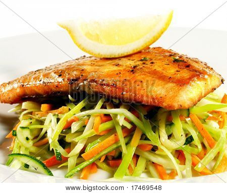 Fillet of Salmon with Julienne Peeler Vegetable and Lemon Slice. Isolated on White Background