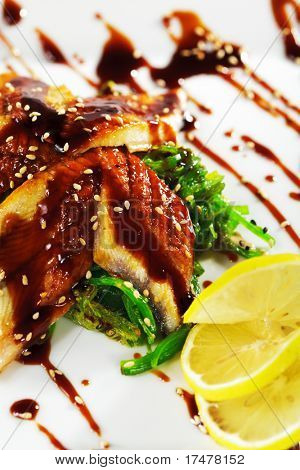Japanese Cuisine - Salad with Sliced Fish and Seaweed. Garnished with Nuts Sauce and Lemon. Topped with Eel Sauce and Sesame