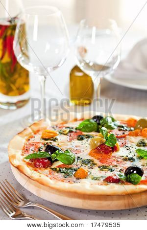 Pizza with Mozzarella Cheese, Fresh Tomato and Pesto Sauce. Served at Restaurant Table