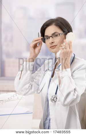 Young female sitting at desk doctor answering phone call.?