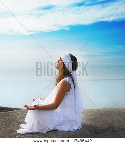 Young girl meditates on the beach