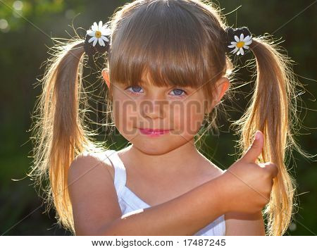Little girl with pigtails and daisy flowers in her hair and thumbs up