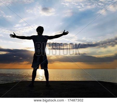 Man standing on the rock with his arms wide open