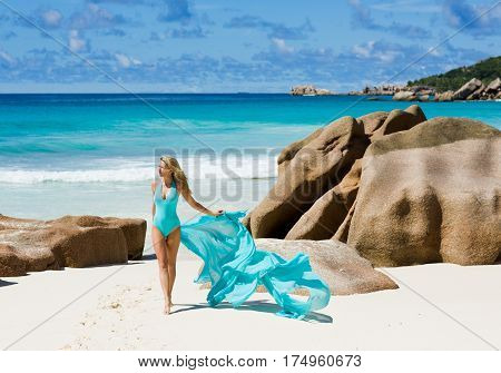poster of Pretty woman in turquoise blue swimsuit, at dream beach, Seychelles