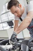 Young maintenance engineer repairing car in automobile store poster