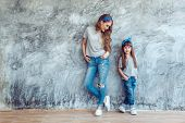 Young beautiful mom with her daughter wearing blank gray t-shirt and jeans posing against rough conc poster