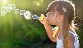 stock photo of blowing  - Little girl blowing soap bubbles - JPG