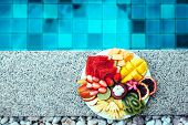 Served fruit plate by hotel pool. Exotic summer diet. Tropical beach lifestyle. poster