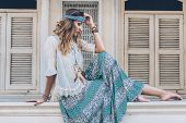 Fashion girl wearing bohemian clothing posing in the old city street. Boho chic fashion style. poster