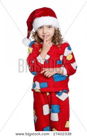 Portrait of Little girl in pajamas and santa hat with silence gesture over white background