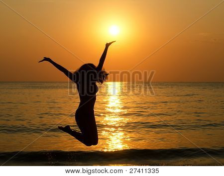 Silhouette of jumping girl against a decline