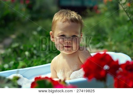 Cute Funny Little Boy Bathing Outdoor In Green Garden Among Flowers
