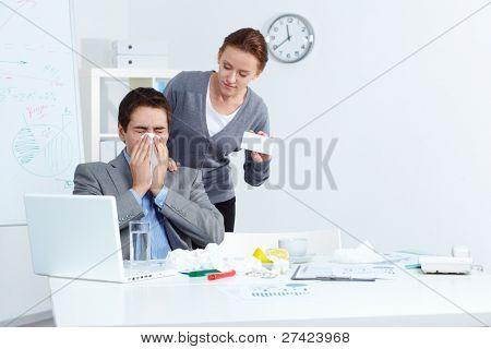 Imagem do empresário doente espirros enquanto seu parceiro, oferecendo-lhe a boa medicina no escritório