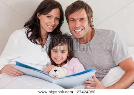 Smiling parents reading a story to their daughter in a bedroom
