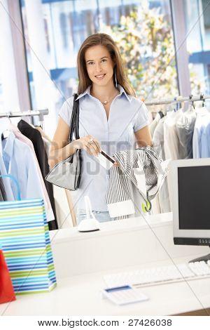glückliche Frau zahlen ihr Einkauf mit Kreditkarte im Kleidung Store, Blick in die Kamera, lächelnd.?