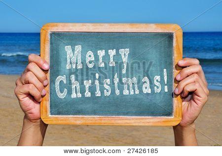 alguém segurando um quadro com a frase feliz Natal escrito por ele na praia