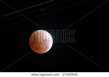 KUALA LUMPUR, MALAYSIA- DECEMBER 10: Lights from the wingtips and fuselage of a passenger jet form light streaks above a full lunar eclipse on the night of December 10, 2011 in Kuala Lumpur, Malaysia.
