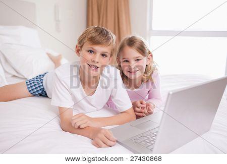 Usando um laptop em um quarto de irmãos