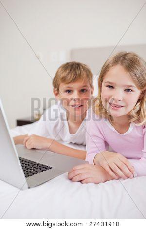 Retrato de crianças bonitos usando um laptop em um quarto