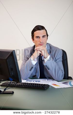 Businessman in thoughts sitting behind his desk
