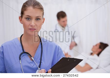 Surgeon standing in patients room with colleague and patient behind her