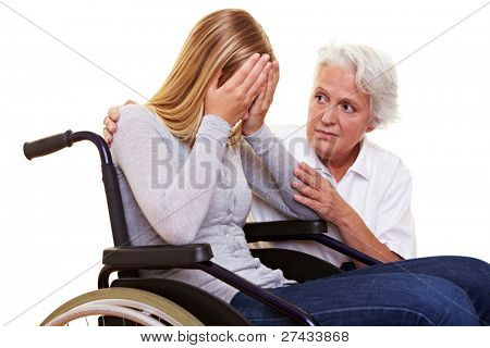 Nurse comforting young crying woman in wheelchair