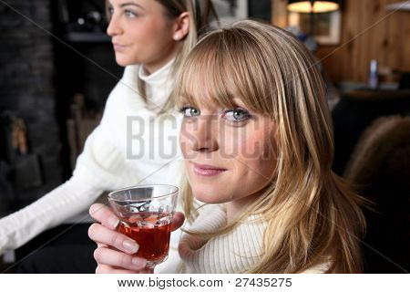 Two female friends relaxing at home with glass of wine