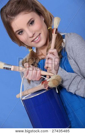 craftswoman painter holding brushes and a painter can