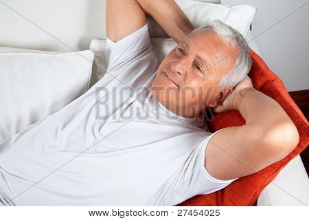 Senior man relaxing on sofa with hands behind his head