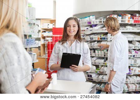 Retrato de mujer farmacéutico con tablet PC mientras que asistir al cliente en el mostrador