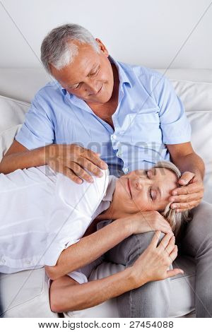 Relaxed woman asleep on husband's lap