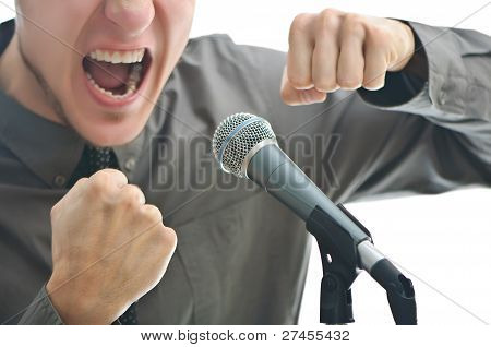 Businessman Screaming In Microphone With His Fist Rased Up Isolated On White Background - Shallow De