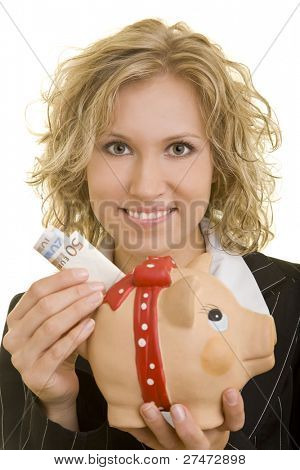 Blonde woman putting money in a piggy bank