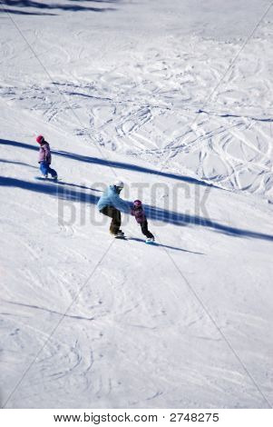 Mother And Children Snowboarding