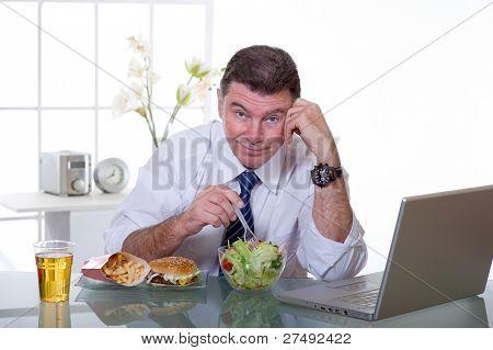 man at office eat green salad healthy food