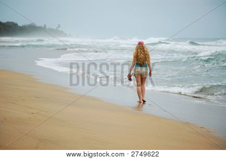 A Young Woman Walks Alone On The Beach