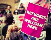 Busy Street Protest March With A Sign Saying Refugees Are Welcome Heren poster