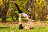 stock photo of tantra  - An attractive man and woman practice tantra yoga in forest - JPG
