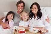 Постер, плакат: Счастливая семья завтрака вместе в спальне