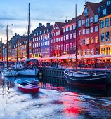 Evening Scene With Boats Moored By Illuminated Nyhavn Harbor Embankment, Copenhagen, Denmark poster