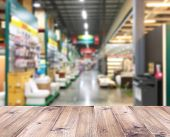 Wood Table Top Over Blurry Background Of Large Furniture Warehouse. Construction Discount Store Inte poster