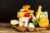 Various Kinds Of Cheese Served On Wooden Table. Wooden Board With Different Kinds Of Delicious Chees poster