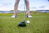 golf club and golf ball on tee, focus on the head of the club and ball. poster