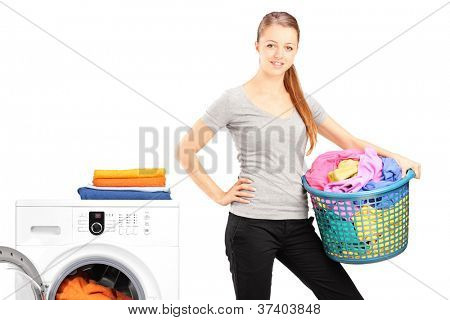 A smiling woman holding a laundry basket next to a washing machine isolated on white background