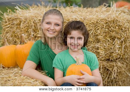 Mother And Daughter With Pumpkins
