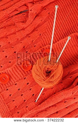 Orange sweater and a ball of wool close-up